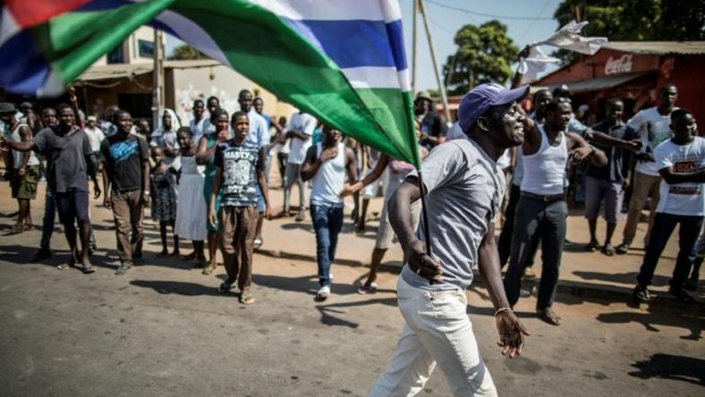 A man waves a Gambian flag while he celebrates the victory of Gambia's opposition candidate Adama Barrow during the Presidential Elections on December 2, 2016, in Serekunda, Banjul