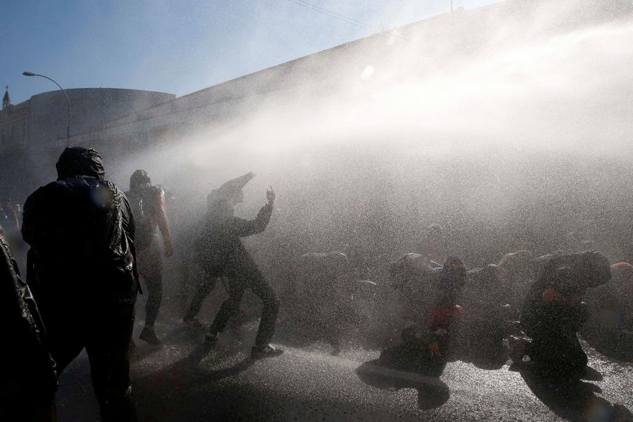 A jet of water from a police water cannon is released on demonstrators during an anti government ral