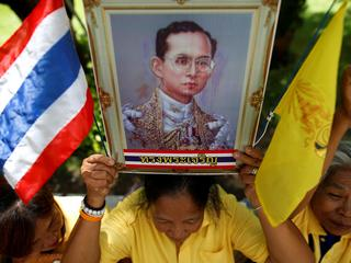 Well-wishers hold a picture of Thailand's King Bhumibol Adulyadej at the Siriraj hospital where he i