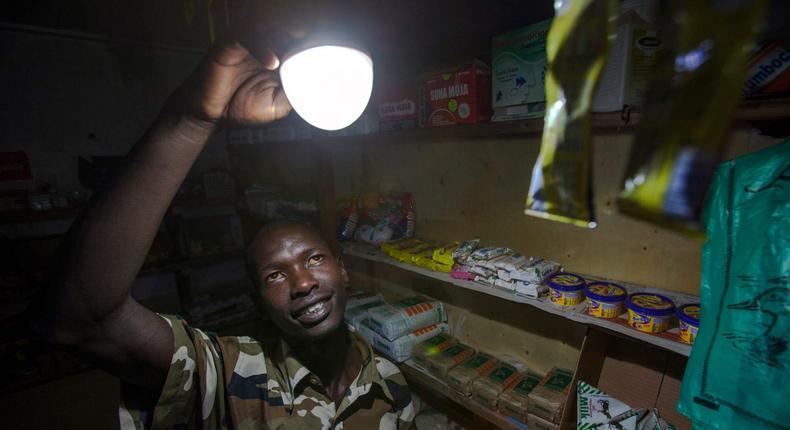 A shopkeeper in Kenya enjoying light emitted by a bulb powered by solar energy.