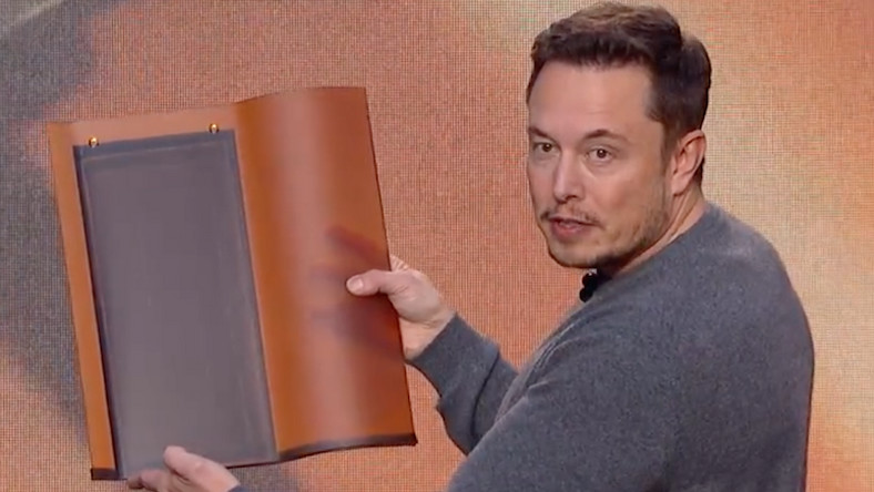 Tesla CEO Elon Musk holds the company's tuscan solar roof tile.