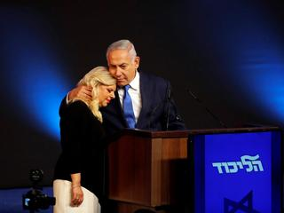 Israeli Prime Minister Benjamin Netanyahu hugs his wife Sara as they stand on stage following the an