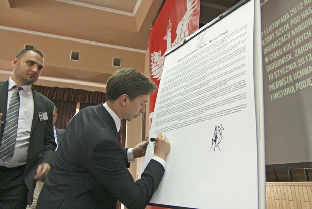 Krzysztof Bosak podpisuje deklarację ideową