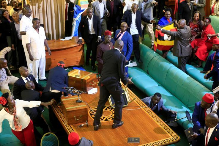 Ugandan opposition lawmakers fight with plain-clothes security personnel in the parliament while protesting a proposed age limit amendment bill debate to change the constitution for the extension of the president's rule, in Kampala, Uganda September 27, 2017. (REUTERS/James Akena)
