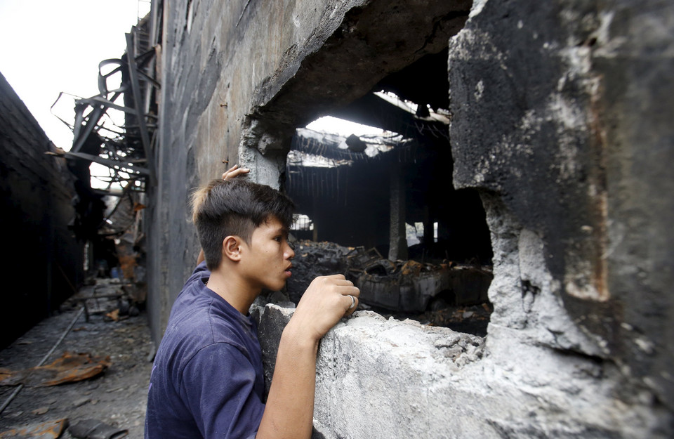 A worker who survived the fire look inside a gutted footwear factory in Valenzuela