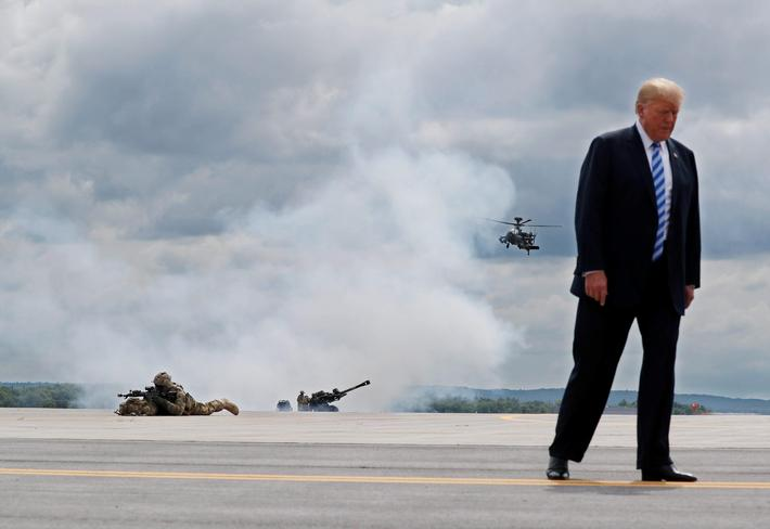 U.S. President Trump observes a demonstration with troops, an attack helicopter and artillery as he