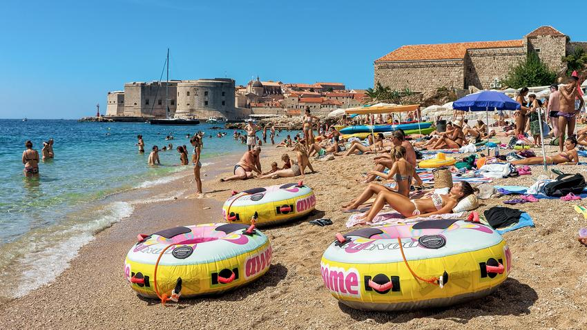 People on beach in Adriatic Sea and Dubrovnik fort