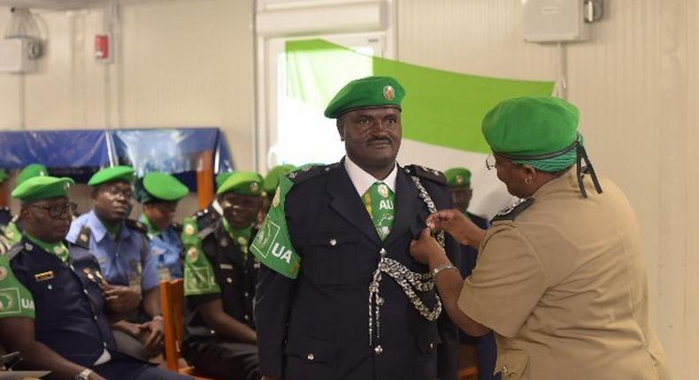Acting AMISOM Police Commissioner pinning medal and handing certificate to an Individual Police Officer