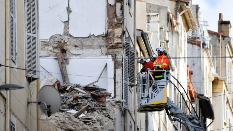 Firemen inspecting buildings near the site where two dilapidated buildings suddenly collapsed this week in the centre of Marseille, southern France