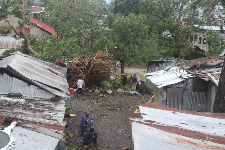 People stand by damaged houses and fallen tree in Comoros. (iNews)
