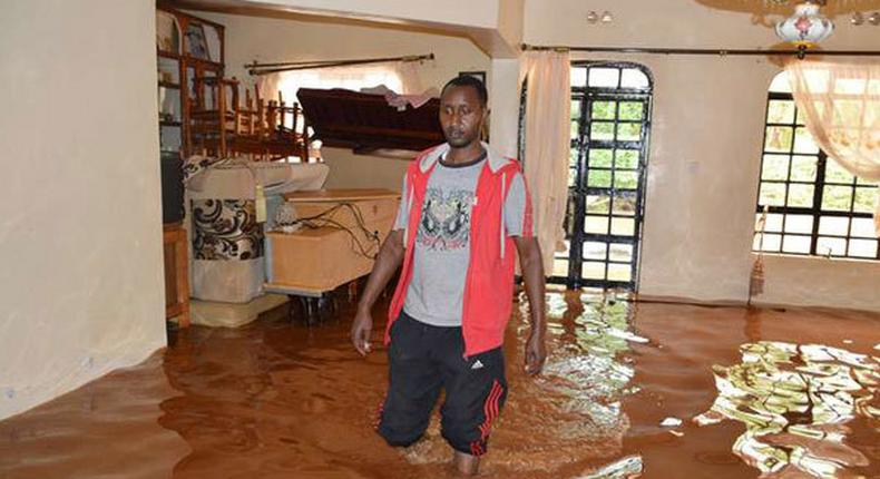 A resident standing inside a flooded home