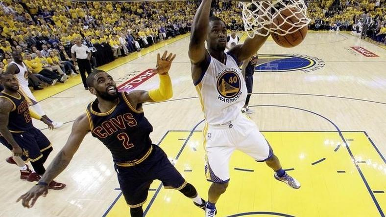 Golden State Warriors forward Harrison Barnes (40) dunks the ball against Cleveland Cavaliers guard Kyrie Irving (2) in game one of the NBA Finals at Oracle Arena.