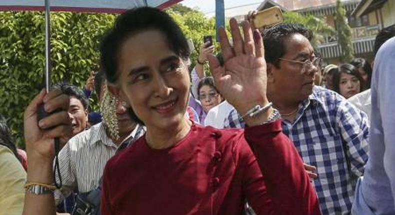 Myanmar pro-democracy leader Aung San Suu Kyi waves at supporters as she visits polling stations at her constituency Kawhmu township November 8, 2015.