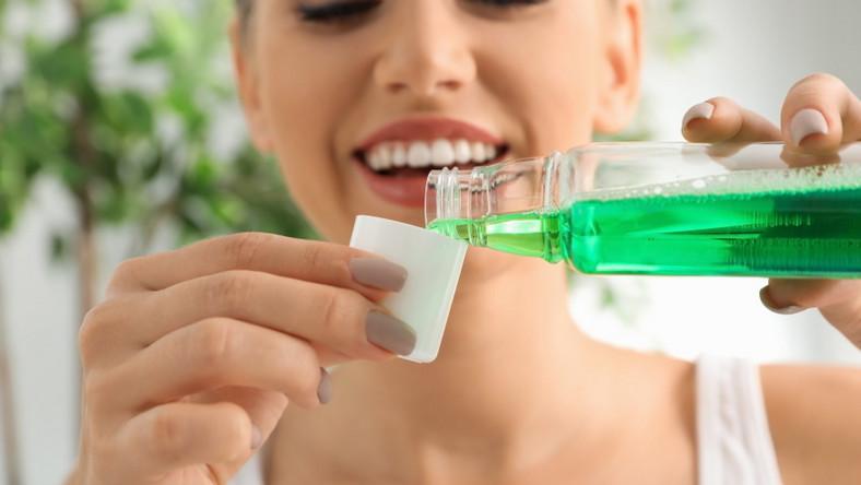 Płukanie jamy ustnej. Kobieta nalewa płyn
