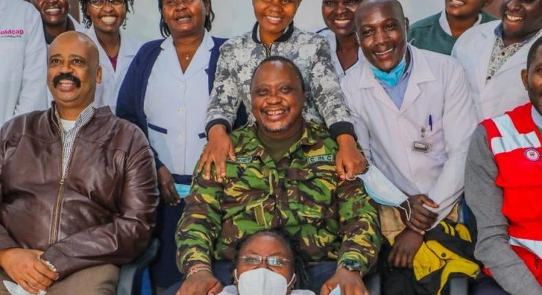 President Uhuru Kenyatta (in camouflage jacket) poses for a photo with health staff in one of the facilities