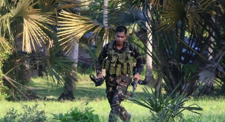 A soldiers runs after retrieving the rifle of a colleague after clashes with militants on Bohol island
