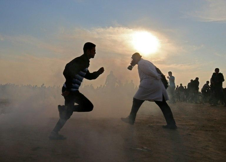 Palestinians run for cover from tear gas during clashes near the border between Israel and Khan Yunis in the southern Gaza Strip on November 9, 2018