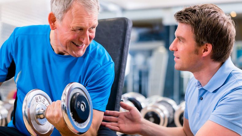 Starszy mężczyzna ćwiczy pod okiem trenera
