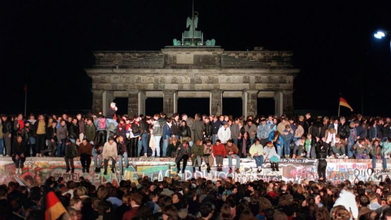 Zdjęcie z 10 listopada 1989. Berlińczycy świętują otwarcie granic przed Bramą Brandenburską w Berlinie. Mur berliński był systemem umocnień o długości ok. 156 km (betonowy mur, okopy, zapory drutowe, miny). W języku enerdowskiej propagandy nazwany antyfaszystowskim wałem ochronnym. Funkcjonował od 13 sierpnia 1961 do 9 listopada 1989 oddzielając Berlin Zachodni od Wschodniego. Padł w nocy z czwartku 9 listopada na piątek 10 listopada 1989, po przeszło 28 latach istnienia. Był on jednym z najbardziej znanych symboli zimnej wojny i podziału Niemiec. Podczas prób przedostania się przez strzeżone urządzenia graniczne do Berlina Zachodniego wielu ludzi zostało zabitych. Różne źródła podają od 136 do 238 śmiertelnych przypadków.