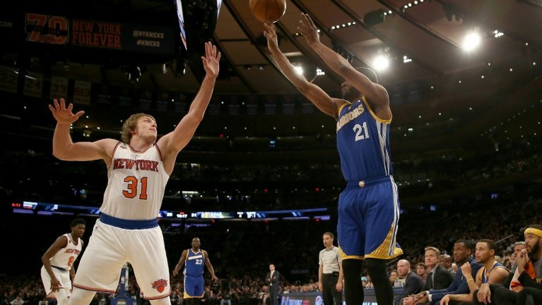 Ron Baker (L) of the New York Knicks tries to block a shot from Ian Clark of the Golden State Warriors at Madison Square Garden on March 5, 2017