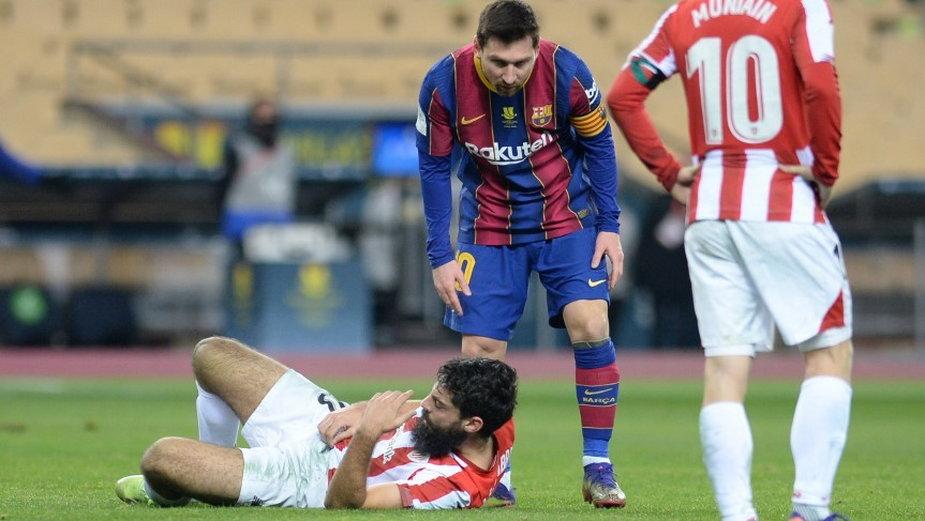 Leo Messi pochyla się nad leżącym Asierem Villalibre