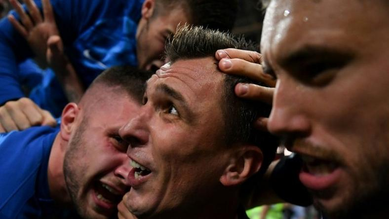 Mario Mandzukic celebrates his winning goal for Croatia after he and his teammates fell on top of AFP photographer Yuri Cortez