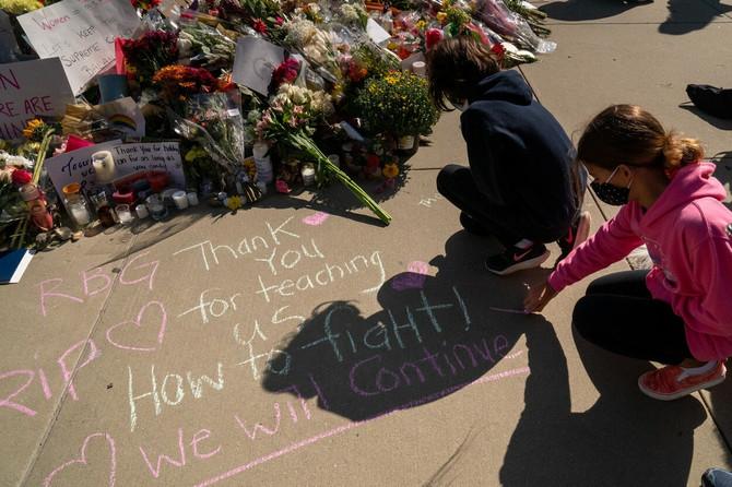 Poštovaoci Rut među kojima ima i dece ostavljaju cveće i poruke ispred Vrhovnog suda