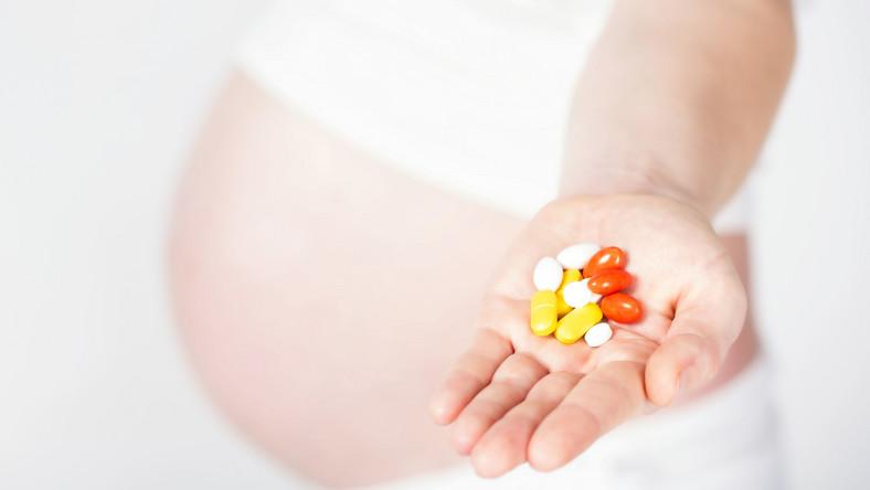 Kobieta w ciąży trzyma leki