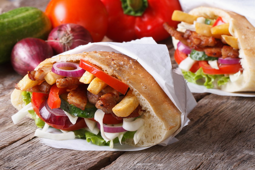 Doner kebab with meat and vegetables in pita wrapped in paper