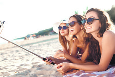 stock-photo-summer-holidays-and-vacation-girls-sunbathing-on-the-beach-girls-doing-selfie-phone-enjoy-summer-597169565
