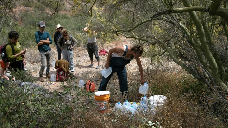 A volunteer for the humanitarian aid organization No More Deaths delivers water along a trail used by undocumented immigrants in the desert near Ajo, Arizona