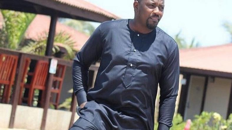 John Dumelo standing by a pool