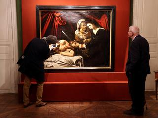 "Visitors looks at a painting entitled ""Judith Beheading Holofernes"" during its presentation in Paris"