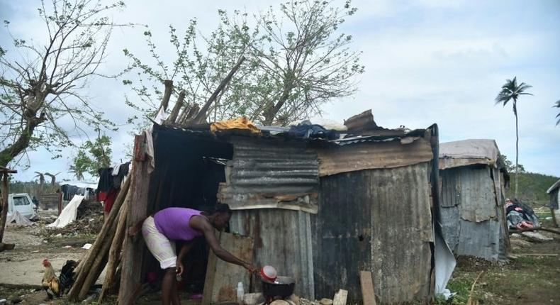A woman prepares food on October 22, 2016 outside her home in the neighborhood of Gebeaux in the commune of Jeremie, southwestern Haiti, which was hit hard by Hurricane Matthew