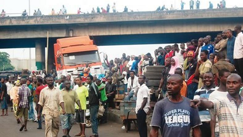 Crowd gathers near a bridge in Ijora Badia during a battle between police and robbers