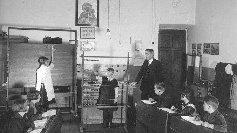 Dzieci i nauczyciel w sali lekcyjnej, lekcja matematyki