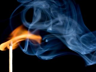 A match creating a flame with smoke