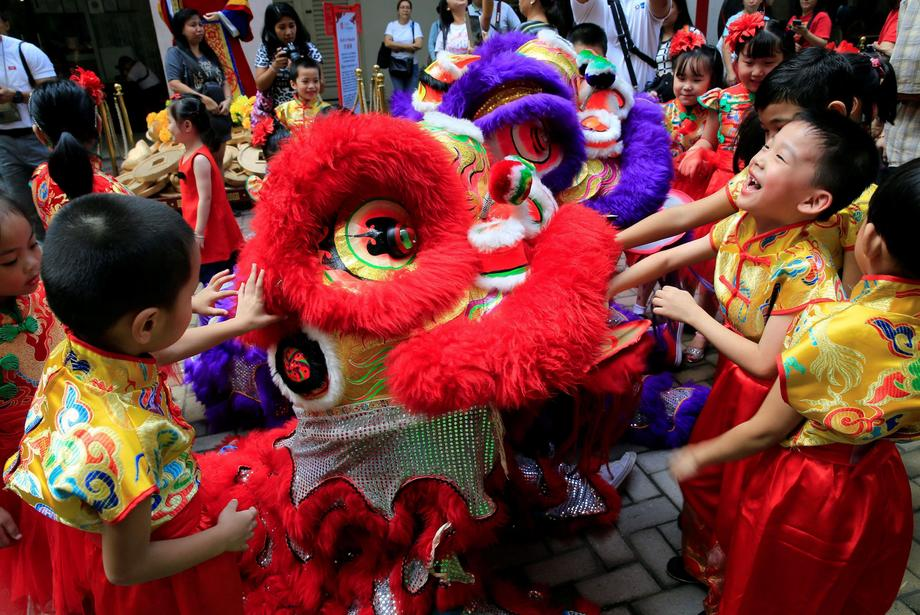 Filipino-Chinese students play with Lion dancers after performing a traditional dance ahead of the L