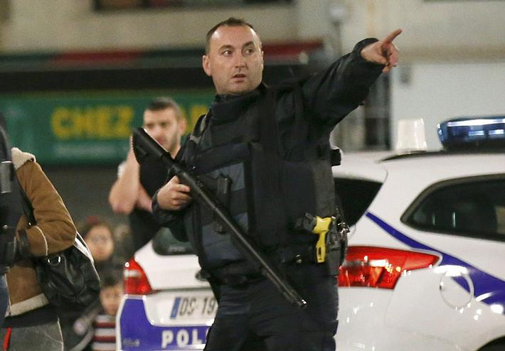 A French policeman points as he evacuates residents during an operation to catch Paris attack fugiti