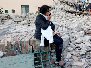 A woman sits amongst rubble following a quake in Amatrice
