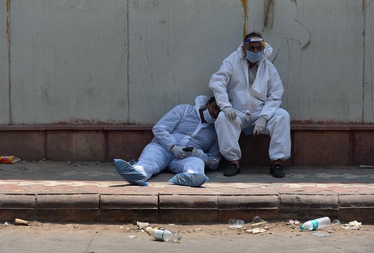 Holtfáradt egészségügyi dolgozók egy kórház mellett Új-Delhiben / EPA/IDREES MOHAMMED