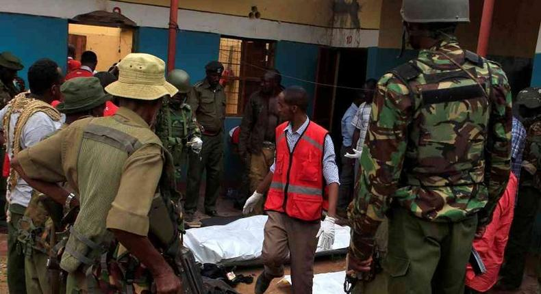 Police officers stand by dead bodies after an attack by Islamist militants from the Somali group al Shabaab in Mandera, Kenya, October 6, 2016.