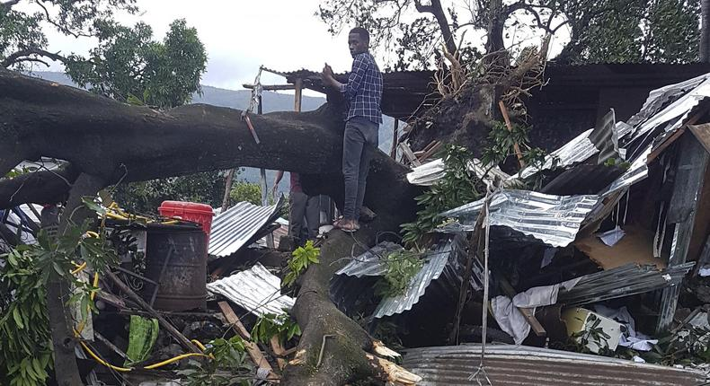 A man stands on fallen trees which damaged his home in Moroni, Comoros, Thursday. (The Spokesman-Review)