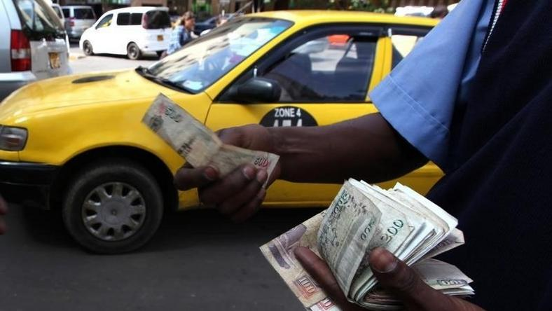 A fuel attendant handles Kenyan shilling notes at a petrol station in the capital Nairobi   REUTERS/Noor Khamis