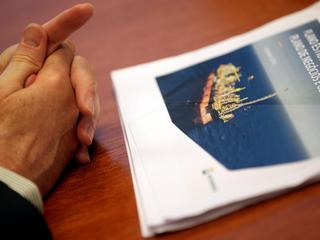The hands of Brazil's state-run oil company Petroleo Brasileiro SA Chief Executive Officer Pedro Parente are pictured next to their business and management plan 2017-2021 as he attends an interview with Reuters in Rio de Janeiro