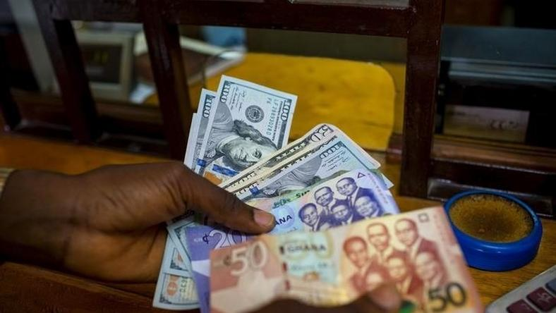 A man trades U.S. dollars for Ghanaian cedis at a currency exchange office in Accra, Ghana, June 15, 2015. Picture taken June 15. REUTERS/Francis Kokoroko