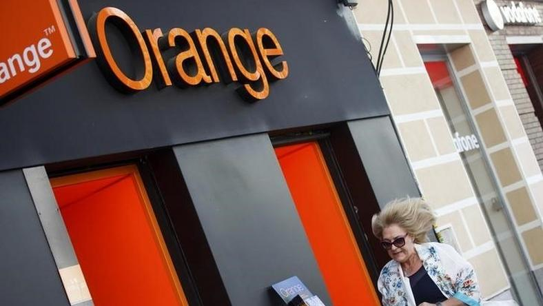 A woman walks past an Orange shop in Madrid, September 16, 2014. REUTERS/Andrea Comas