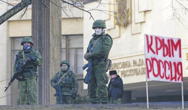 """Symferopol w 2014 r. Uzbrojeni mężczyźni stoją przed budynkiem lokalnego parlamentu, w tle transparent z napisem """"Krym to Rosja"""""""