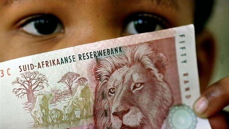 A South African child holds a 50 rand note in a file picture - RTXI6ZY