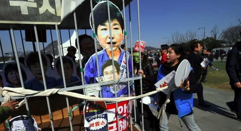 Anti-government activists carry a mock jail containing a cardboard cut-out of South Korea's President Park Geun-Hye of Park in Seoul on March 10, 2017 after the Constitutional Court upheld her impeachment
